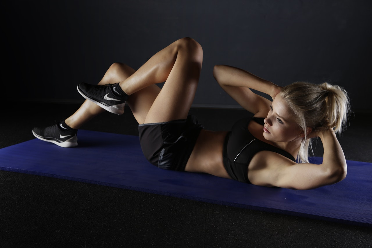 woman working out using the best exercises for losing belly fat